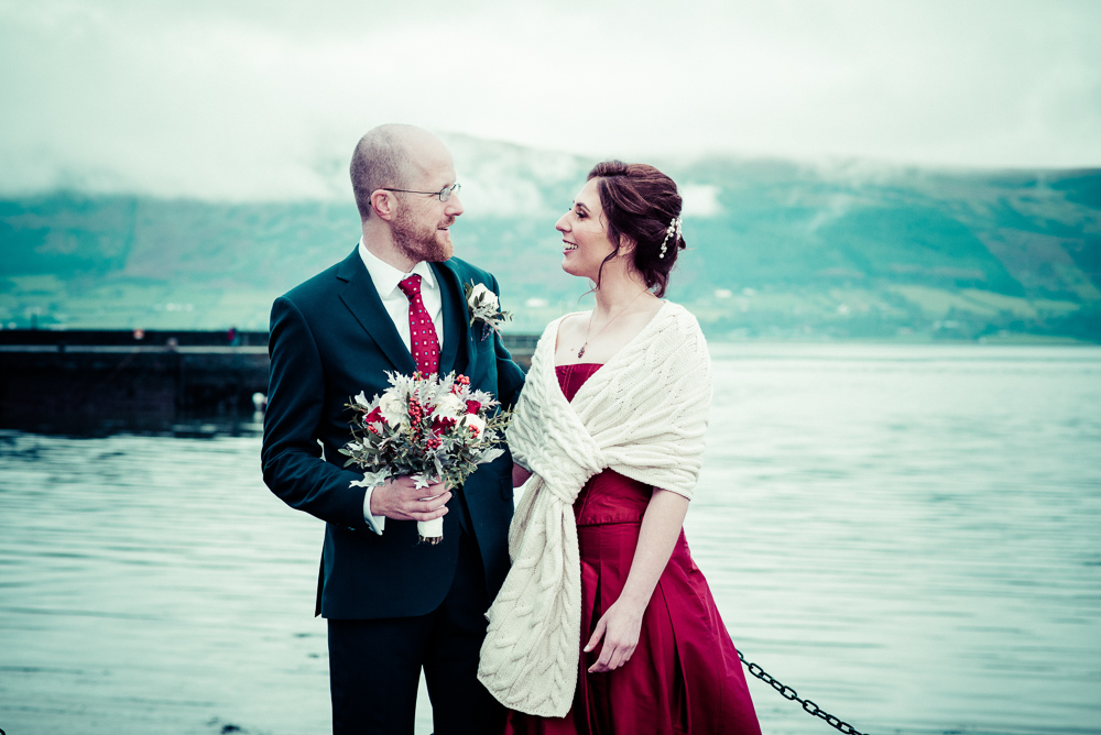 The bride and groom pose for a wedding photograph in front of Carlingford Lough at a micro wedding in Ireland