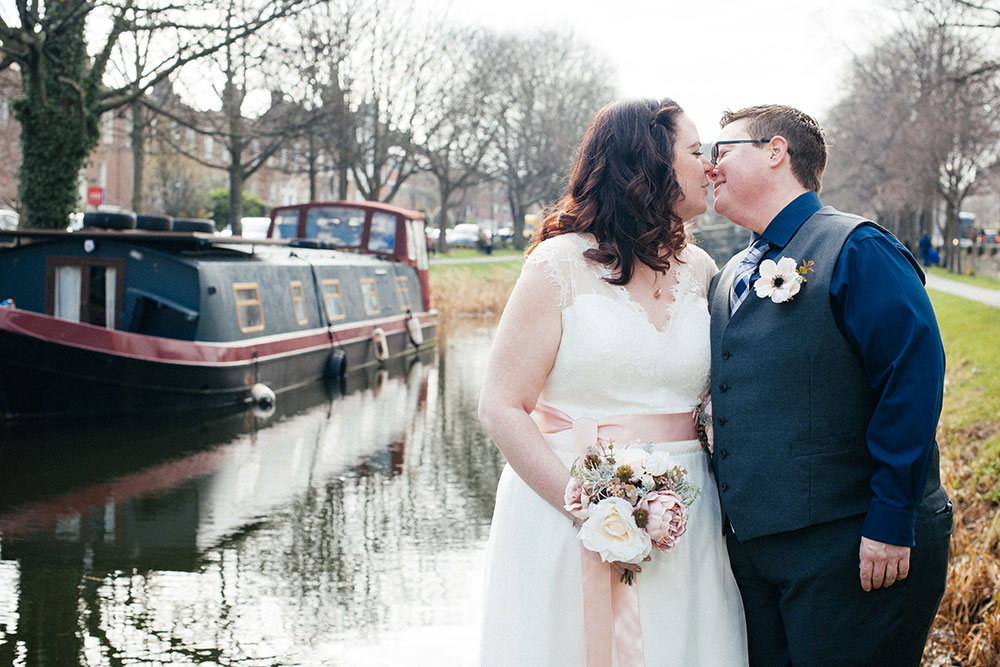 A couple exchange a kiss on the banks of the Grand Canal during their LGBT Dublin Wedding