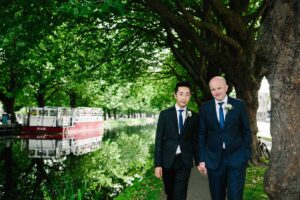 Two grooms photographed standing along the banks the Grand Canal during their LGBT Dublin Wedding.