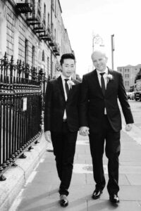 LGBT wedding photographer photographs two grooms walking through Dublin on their wedding day