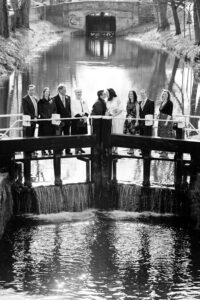 A couple photographed with their families standing on the lock crossing the Grand Canal during their LGBTQ Wedding
