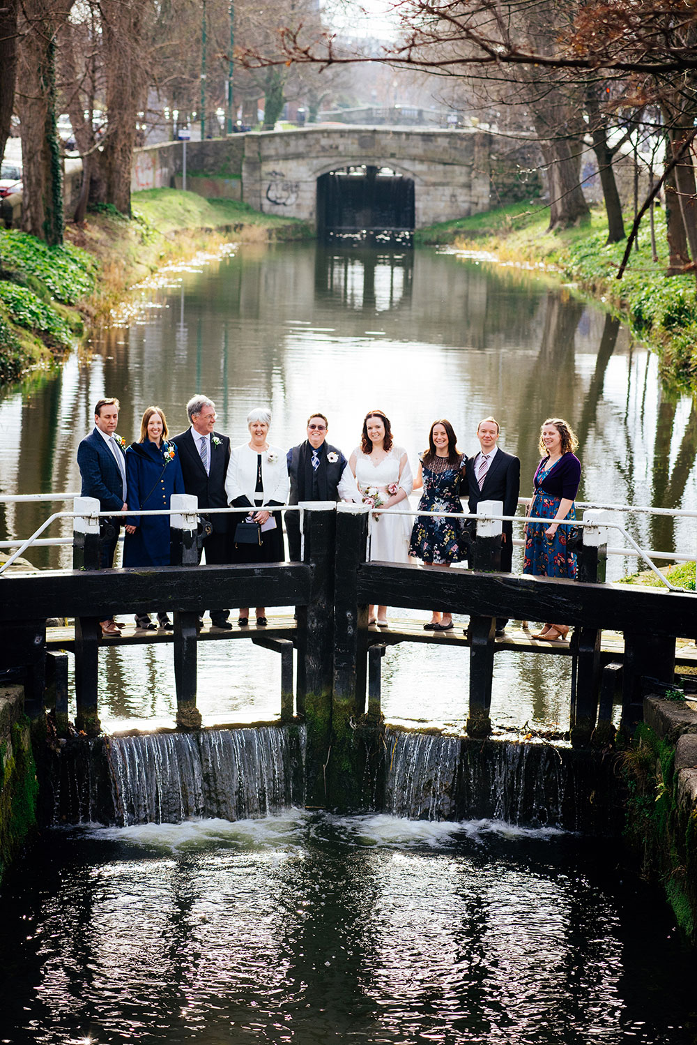 A couple photographed with their families standing on the lock crossing the Grand Canal during their LGBTQ Dublin Wedding