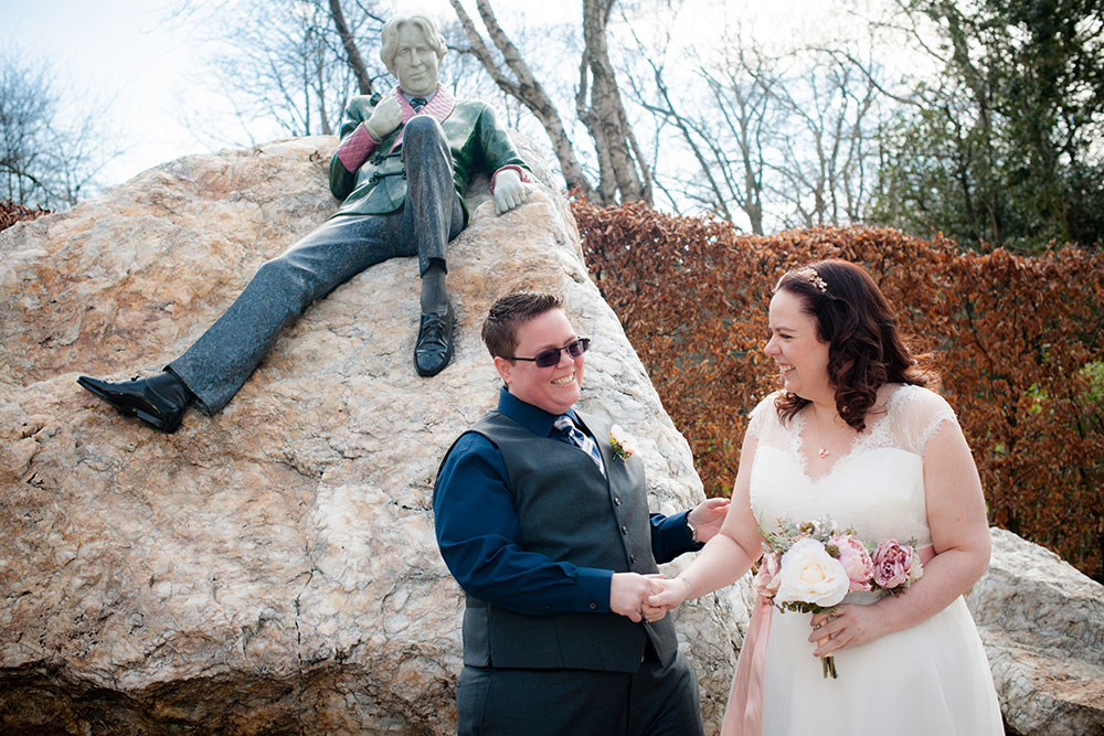 LGBTQ Wedding photography of a couple standing by the statue of Oscar Wilde in Merrion Square in Dublin on their wedding day.