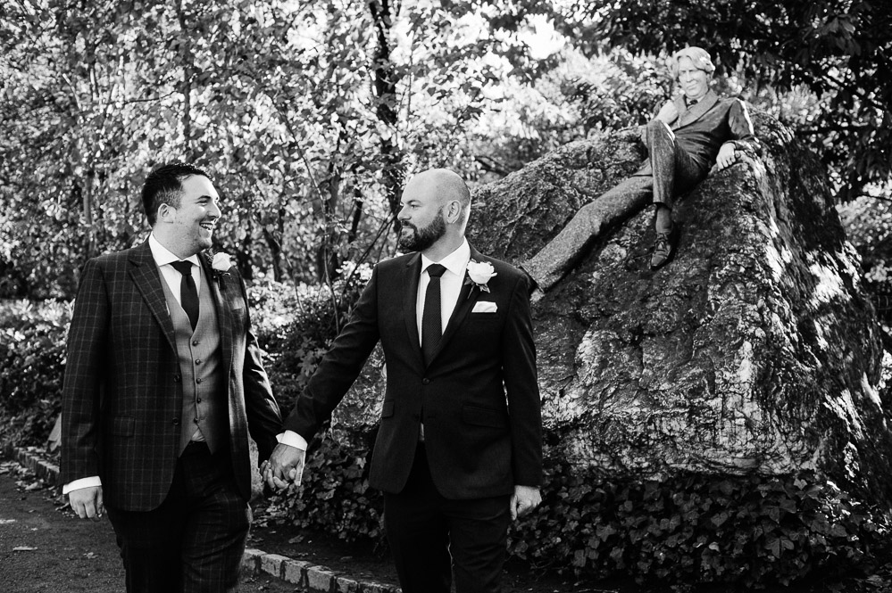 LGBTQ Wedding Photography of two grooms in front of the Oscar Wilde Statue in Merrion Square Park in Dublin on their wedding day.