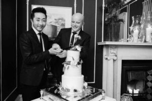 LGBTQ wedding photography of two grooms cutting their wedding cake during their wedding reception at No. 25 Fitzwilliam Place in Dublin