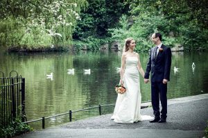 The bride and groom pose for a wedding photograph by the pond in St.Stephen's Green before their Fallon & Byrne Wedding Reception