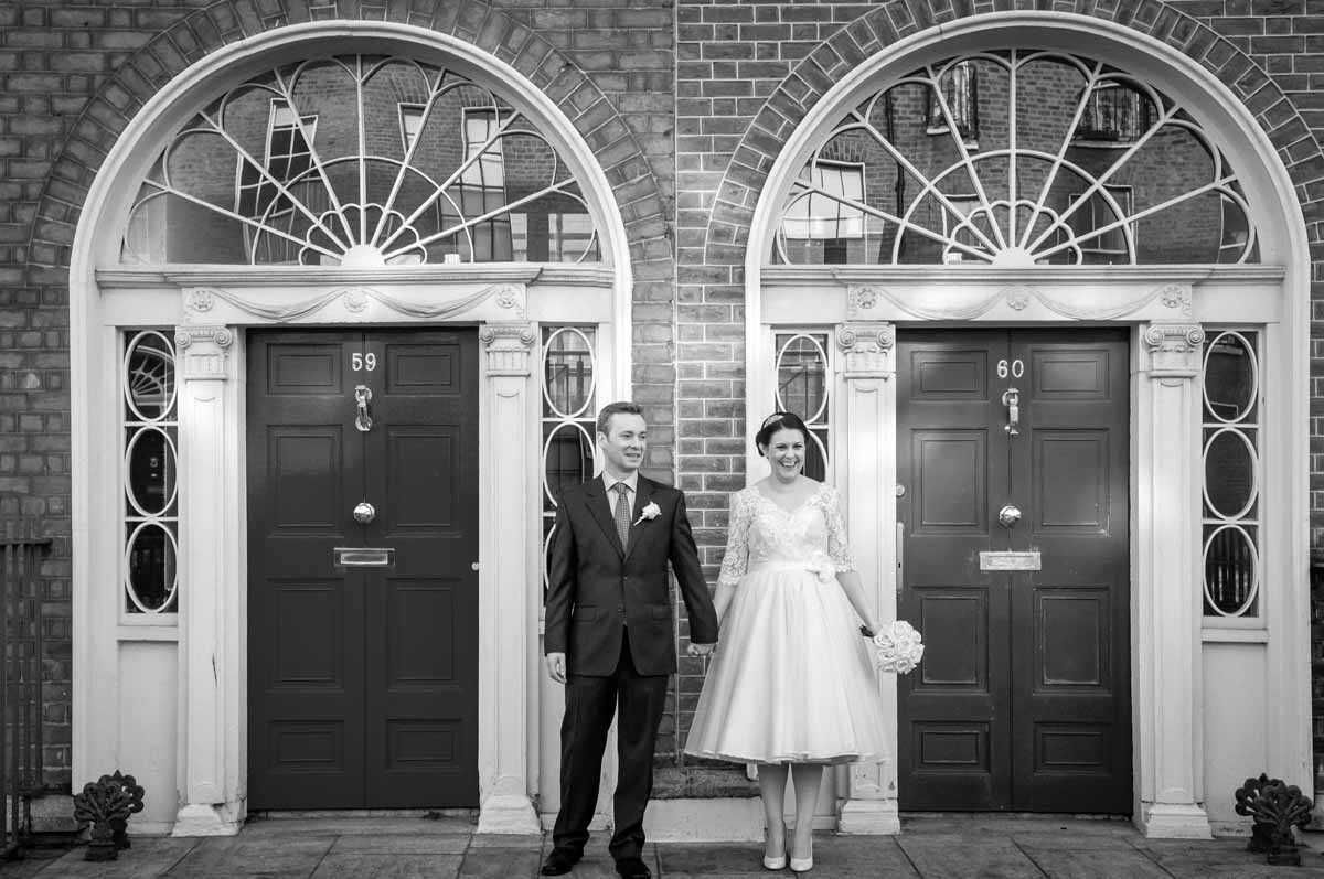 The bride and groom pose for some Registry Office Wedding Photography in front of a Georgian Door before their registry office wedding