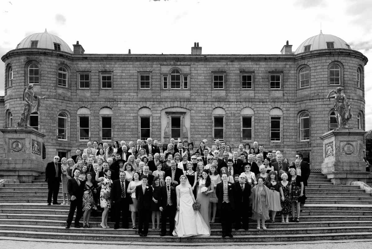Wedding guests pose for a Powerscourt Wedding Photograph on the steps in the grounds of the estate gardens