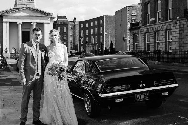 The bride and groom pose with a vintage car after been married at the Registry Office in Dublin