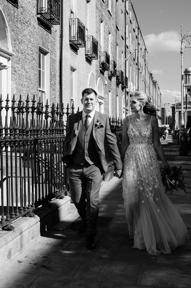 The bride and groom walk through Dublin following their registry office wedding ceremony