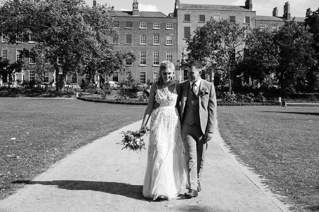 The bride and groom walk through Merrion Square Park in Dublin
