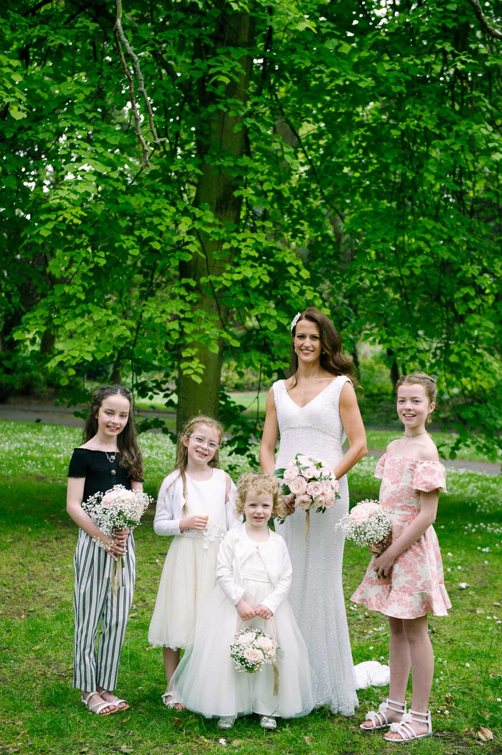 The bridal party pose for a wedding photograph in St. Stephen's Green during a wedding at Shelbourne Hotel