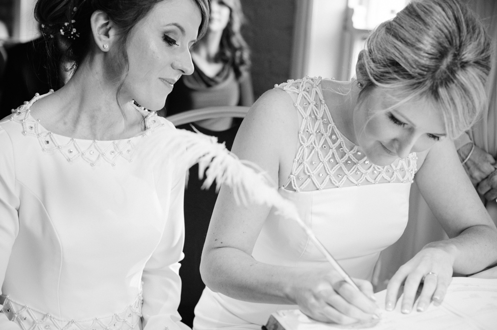 Two brides sign the marriage registry at their LGBT wedding ceremony in Dublin