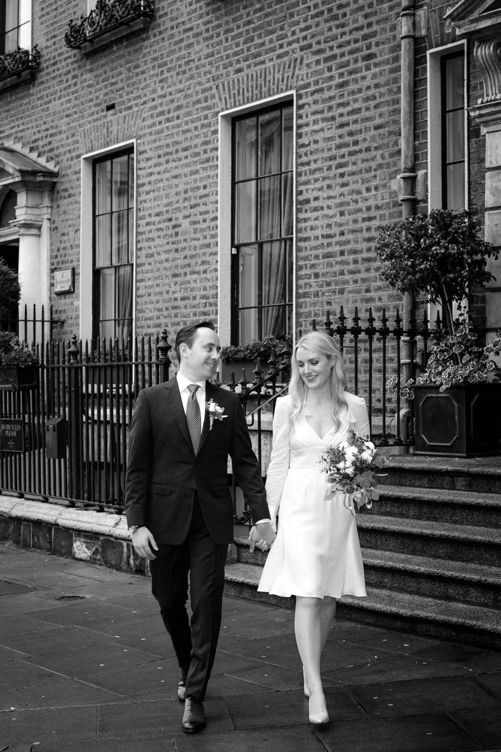 The bride and groom walk hand in hand along Merrion Row in Dublin during their Merrion Hotel wedding