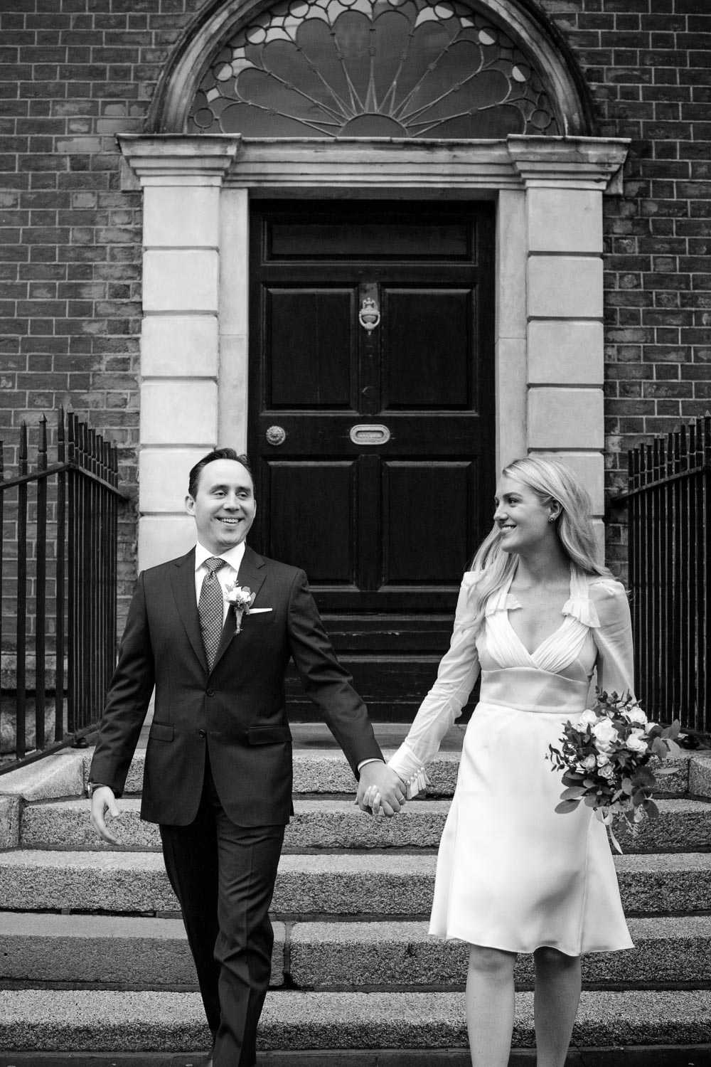 The bride and groom walk down the steps of the Merrion Hotel for a photograph during their Merrion Hotel Wedding