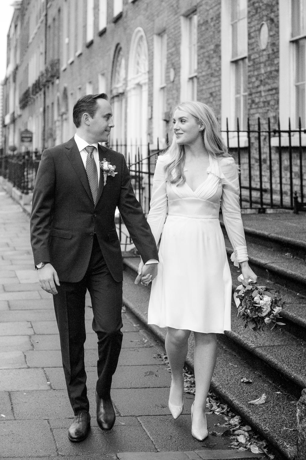 The bride and groom walk hand and hand through Georgian Dublin for a photograph during their Merrion Hotel wedding