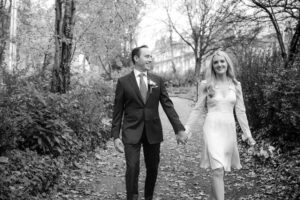 The bride and groom walk hand and hand through Merrion Square Park in a Merrion Hotel wedding photograph