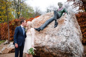 The bride and groom exchange a kiss under the watchful eye of Oscar Wilde in Merrion Square Park in a Merrion Hotel Wedding Photograph
