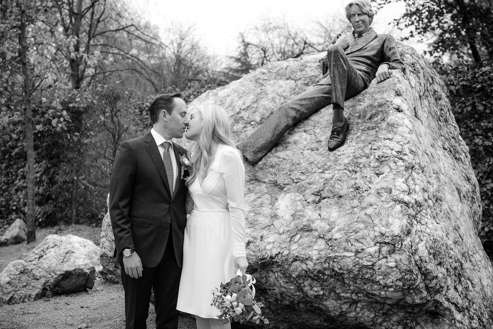 The bride and groom exchange a kiss on their wedding day under the statue of Oscar Wilde in Merrion Square Park in a Merrion Hotel Wedding Picture