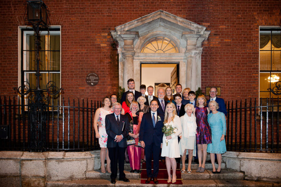Guests at a Merrion Hotel wedding pose for a group photograph on the steps of the hotel