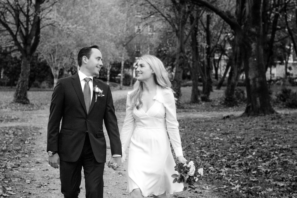 The bride and groom walk through Merrion Square park before their wedding at The Merrion Hotel